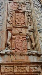 cropped carving at door featuring family and Scottish national heraldry
