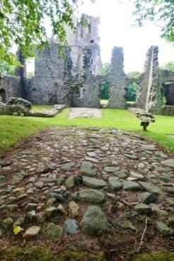 Original roughly paved road to the castle with pebbles and boulders with the east range of the early 17th C additions to the castle